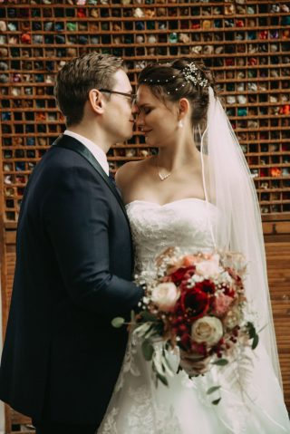 Braeutigam kuesst braut auf die Stirn. Braut traegt weisses Brautkleid und Blumenstrauss